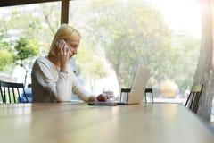 Bella ragazza con i capelli di scarsità che parla su un telefono cellulare mentre sedendosi in un caffè Fotografia Stock