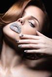 Bella ragazza con i chiodi e le labbra luminosi dei cristalli, dei cigli lunghi e dei riccioli Fronte di bellezza immagine stock