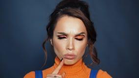 Bella ragazza con i cigli dipinti che aggrotta le sopracciglia Espressione femminile del fronte stock footage