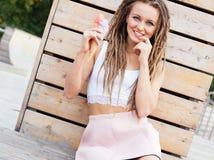 Bella ragazza con i dreadlocks in gonna rosa che si siede sulla veranda e che mangia cono gelato variopinto su una sera calda di  Immagini Stock Libere da Diritti