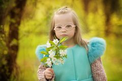Bella ragazza con i fiori della molla della tenuta di sindrome di Down Immagine Stock Libera da Diritti