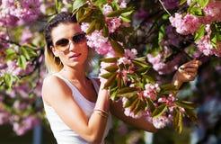 Bella ragazza con i fiori, magia della primavera Fiori di rosa di Sakura Con la pelliccia bianca di fascino e gli occhiali da sol Fotografia Stock Libera da Diritti
