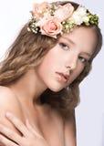 Bella ragazza con i fiori nei suoi capelli e trucco rosa Immagine della primavera Fronte di bellezza Immagini Stock