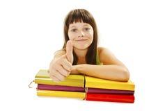Bella ragazza con i libri di banco sulla tabella, mostrante segno GIUSTO Fotografia Stock