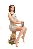 Bella ragazza con un libro che si siede su un mucchio dei libri Immagini Stock