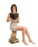 Bella ragazza con un libro che si siede su un mucchio dei libri Fotografia Stock