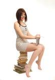 Bella ragazza con un libro che si siede su un mucchio dei libri Fotografia Stock Libera da Diritti