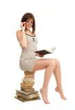 Bella ragazza con un libro che si siede su un mucchio dei libri Immagine Stock