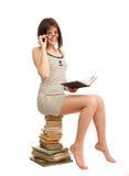 Bella ragazza con un libro che si siede su un mucchio dei libri Fotografie Stock Libere da Diritti