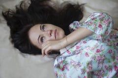 Bella ragazza con i suoi capelli sul letto Immagine Stock