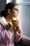 Bella ragazza con i vetri che beve il caffè di mattina davanti alla finestra Immagini Stock