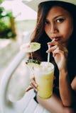 Bella ragazza con il cappello, bevente il succo di ananas fresco e di rinfresco, vacanza di vacanza estiva immagini stock