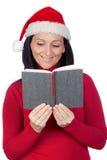 Bella ragazza con il cappello di natale che legge un libro Immagini Stock Libere da Diritti