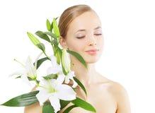 Bella ragazza con il fiore del giglio su bianco Immagine Stock
