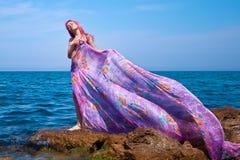 Bella ragazza con il flusso continuo del vestito sulla spiaggia fotografie stock libere da diritti