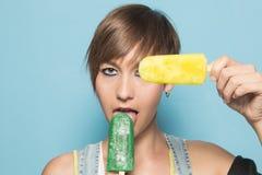 Bella ragazza con il gelato su un fondo blu fotografia stock libera da diritti