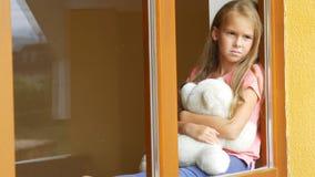 Bella ragazza con il giocattolo molle che guarda attraverso la finestra archivi video