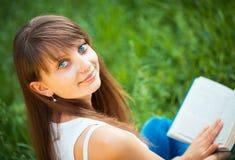 Bella ragazza con il libro nella fine del parco su Fotografia Stock