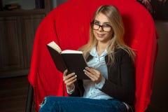 Bella ragazza con il libro in sedia Fotografia Stock Libera da Diritti