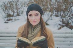 Bella ragazza con il libro sul banco di parco nell'inverno Fotografie Stock Libere da Diritti