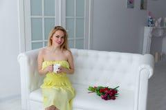 Bella ragazza con il mazzo del tulipano ed il tè della tazza 8 marzo Fotografie Stock Libere da Diritti