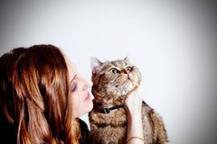 Bella ragazza con il suo gatto su fondo bianco La gente ed animali domestici lifestyle Immagine Stock