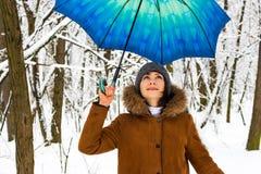 Bella ragazza con l'ombrello blu nel concetto nevoso delle precipitazioni nevose della foresta Donna sotto la pioggia bagnata del immagine stock