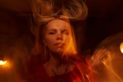 Bella ragazza con la fiamma su fondo nero Immagini Stock Libere da Diritti