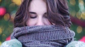 Bella ragazza con la grande sciarpa che sorride all'aperto nell'inverno, fondo della luce di natale Ritratto all'aperto di invern video d archivio