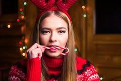 Bella ragazza con la lecca-lecca e le luci festive fotografia stock libera da diritti