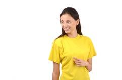 Bella ragazza con la maglietta gialla che indica il lato. Fotografia Stock Libera da Diritti