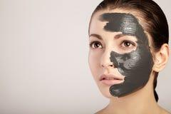 Bella ragazza con la maschera dell'argilla sul suo fronte Immagine Stock