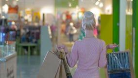 Bella ragazza con la posa dei sacchetti della spesa, flirtante nel centro commerciale video d archivio