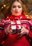 Bella ragazza con la scatola attuale e le luci festive fotografia stock libera da diritti