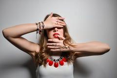 Bella ragazza con le labbra luminose nello studio Bigiotteria dei gioielli - orecchini, braccialetto, collana rossa fotografia stock