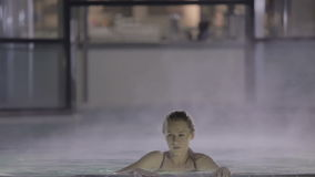 Bella ragazza con nuoto perfetto del corpo attraverso il vapore nello stagno video d archivio