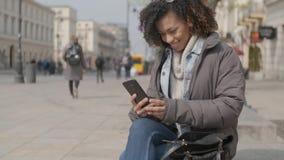 Bella ragazza con taglio di capelli di afro che si siede sul banco alla via della citt video d archivio