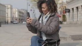Bella ragazza con taglio di capelli di afro che si siede sul banco alla via della citt? archivi video