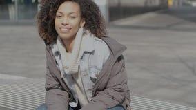 Bella ragazza con taglio di capelli di afro che si siede sul banco alla via della città video d archivio