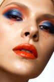 Bella ragazza con trucco colorato luminoso e le labbra arancio Fronte di bellezza fotografia stock libera da diritti