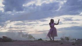 Bella ragazza con trucco di luminosità in vestito rosa che balla nella foschia dalle bombe fumogene all'aperto Il ballo della a stock footage