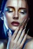 Bella ragazza con trucco dorato e d'argento creativo di scintillio, arte lunga dei chiodi Fronte di bellezza Fotografia Stock
