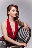 Bella ragazza con trucco luminoso sulla sedia Immagini Stock