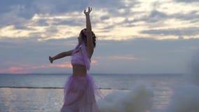 Bella ragazza con trucco luminoso in vestito rosa che balla nella foschia viscosa dalle bombe fumogene all'aperto Il ballo della  stock footage