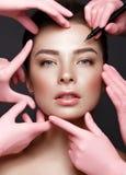 Bella ragazza con trucco nudo naturale con gli strumenti cosmetici in mani Fronte di bellezza fotografia stock