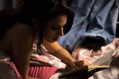 Bella ragazza con trucco professionale che legge un libro Immagini Stock