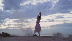 Bella ragazza con trucco scintillante in vestito rosa che balla nella foschia dalle bombe fumogene sulla banca del fiume E stock footage