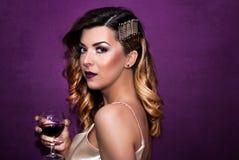 Bella ragazza con un bicchiere di vino disponibile con l'acconciatura dorata riccia che posa davanti alla parete porpora fotografia stock