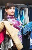 Bella ragazza con un'bracciata dei vestiti in sue mani Immagine Stock Libera da Diritti