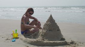 Bella ragazza con un castello incorporato della sabbia su una spiaggia tropicale, donna nei precedenti di un mare di estate del c stock footage